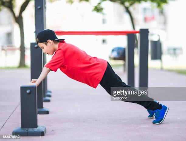 young boy make sport workout on the street - tighten stock pictures, royalty-free photos & images