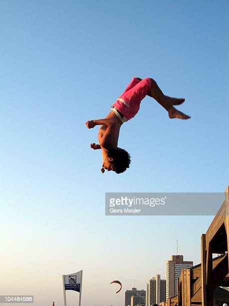 Young boy makes an acrobatic jump from a sun shade pavilion on the sea shore.