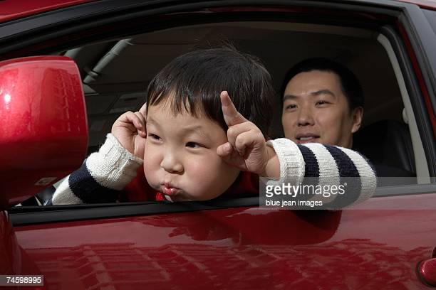Young boy makes funny faces in the side-view mirror of a car while his father watches