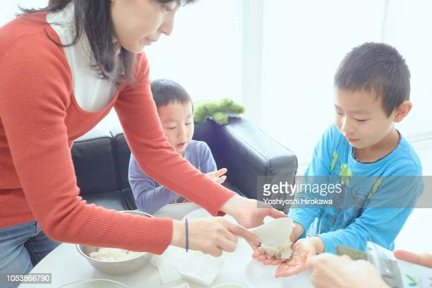 young boy making breakfast with family in home - accompagnement photos et images de collection