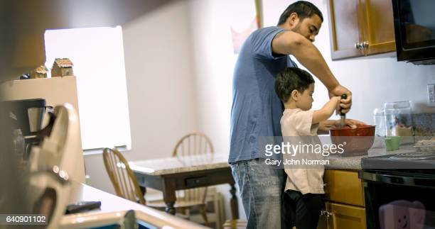 Young boy making cupcakes in kitchen with dad.