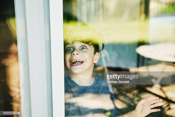 young boy making face though window - personas sin dientes fotografías e imágenes de stock