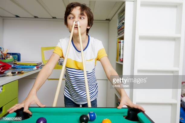 young boy making faces with billiard cue in his nose - insanity stock pictures, royalty-free photos & images