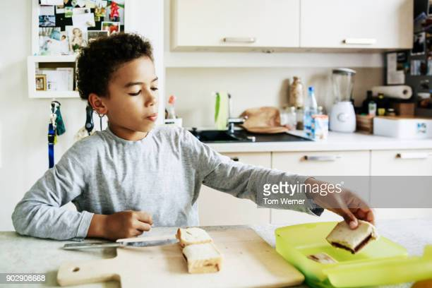 Young Boy Making Himself Packed Lunch Before School