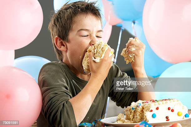 Young boy (10-11 years) making mess with birthday cake