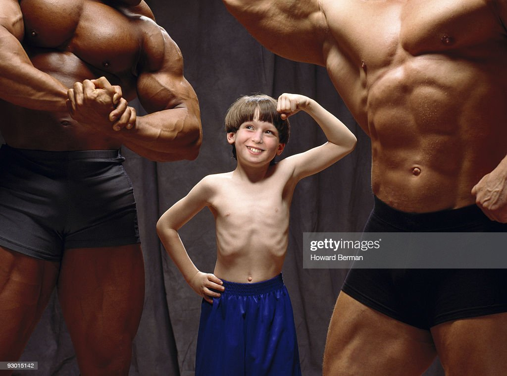 Young boy making muscles with body builders. : Stockfoto