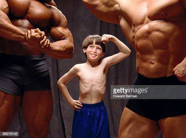 Young boy making muscles with body builders.