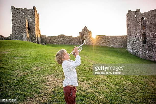 a young boy making music in a castle - bugle stock pictures, royalty-free photos & images