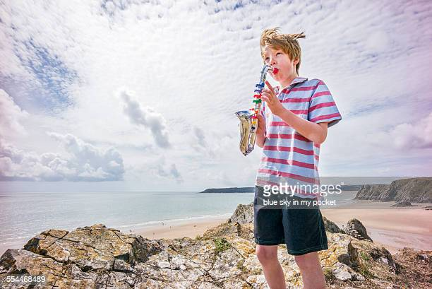 A young boy making music on a beach holiday