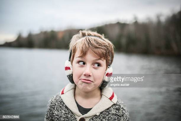 young boy making silly face wearing earmuffs - angela auclair stock pictures, royalty-free photos & images