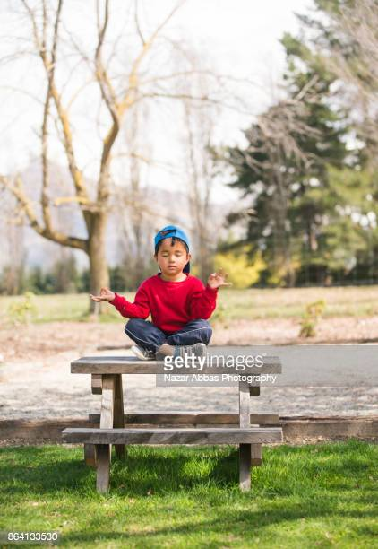 Young boy meditating zen like in a park.