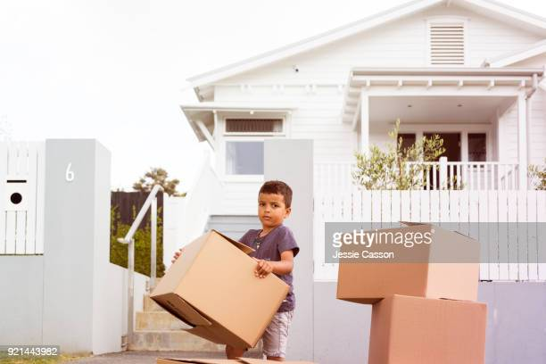 young boy moves packing boxes outside family home