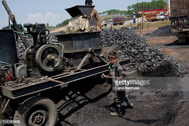 A young boy named Fight believed to be 8 years old shovels coal at a depot on April 15 2011 near Lad Rymbai in the district of Jaintia Hills India...