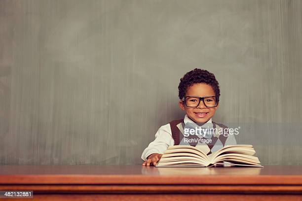 Young Boy Nerd Reading at Desk in Classroom