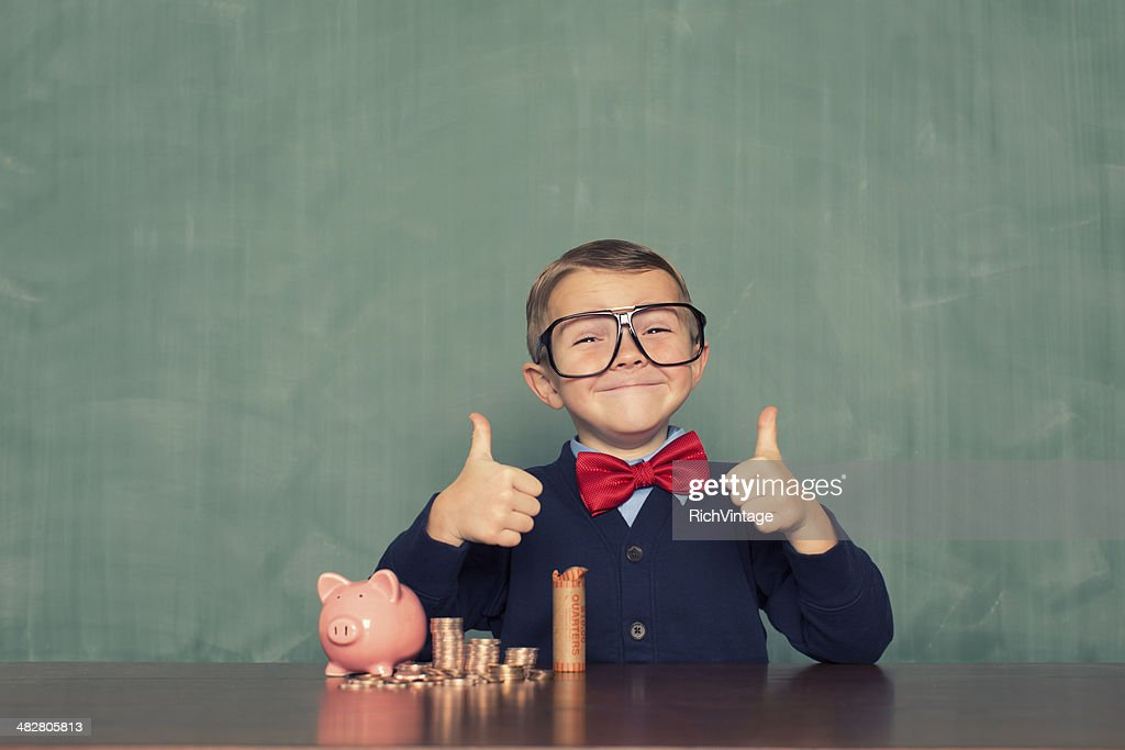 Young Boy Nerd Saves Money in His Piggy Bank : Stock Photo