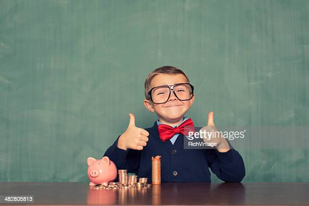 young boy nerd saves money in his piggy bank - piggy bank stock photos and pictures