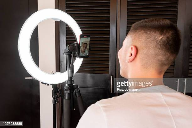 young boy of latin ethnicity shows things on social networks behind a ring of light, during the covid-19 - general view stock pictures, royalty-free photos & images