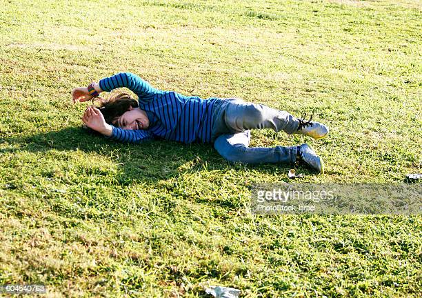 young boy of six, rolls down a grassy hill - manches longues photos et images de collection