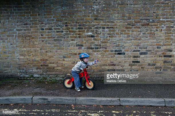 Young boy on a bike pointing a toy gun