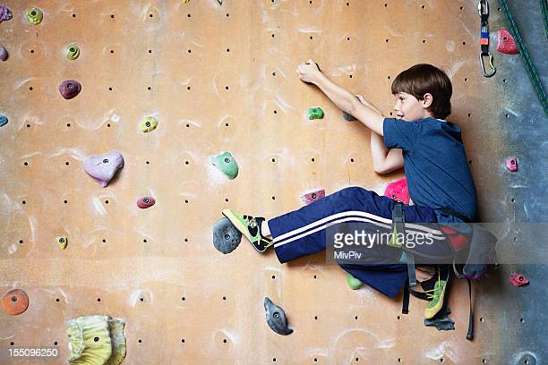 Young boy on a rock climbing wall