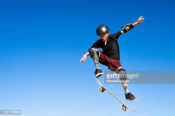 young boy on a skateboard jumping into the air - ollie pictures stock pictures, royalty-free photos & images