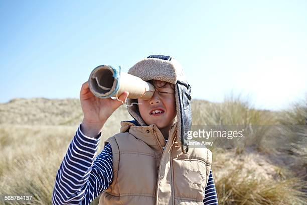 young boy on beach, looking through pretend telescope - nur jungen stock-fotos und bilder