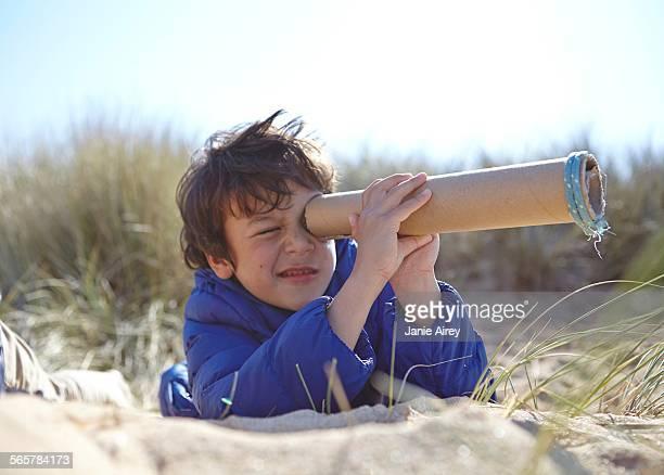 Young boy on beach, looking through pretend telescope