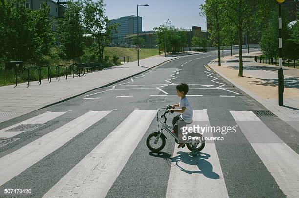 young boy on bicycle - zebra crossing stock pictures, royalty-free photos & images