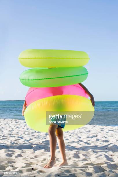 Young boy on the beach wearing four inflatable rings