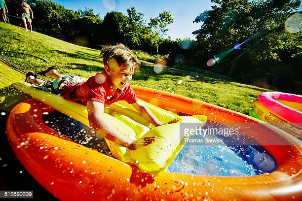 Young boy on water slide in backyard of home