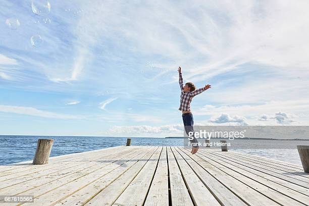 Young boy on wooden pier, jumping to reach bubbles
