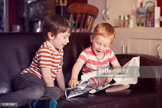 Young boy opening present from his brother