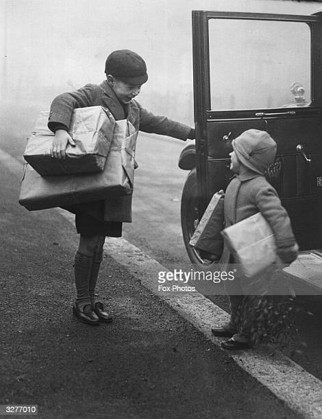 A young boy opens the car door for his sister after returning from a Christmas shopping expedition