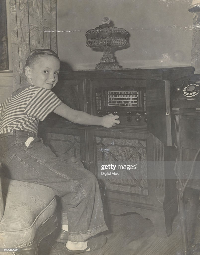 Young Boy Operating a Radio in His Living Room : Stock Photo