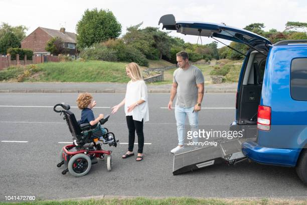 young boy operating wheelchair to access car ramp - mode of transport stock pictures, royalty-free photos & images