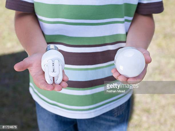 Young boy outdoors holding an environmentally sound lightbulb and a standard lightbulb in his hands