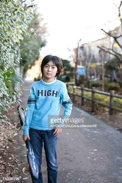 Young boy outdoors holding skateboard