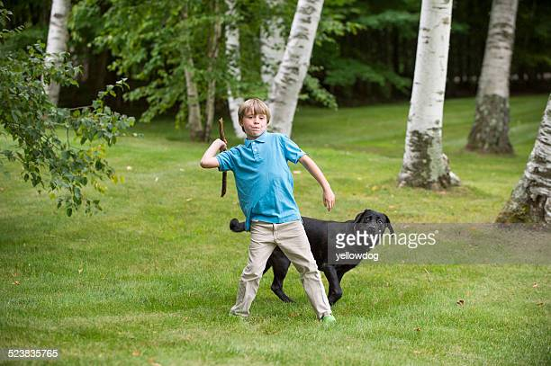 Young boy outdoors, throwing stick for dog