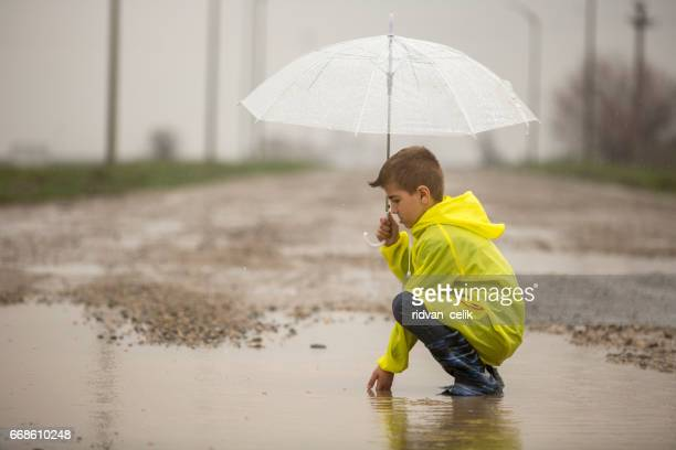 a young boy outside in the rain - heavy rain stock photos and pictures