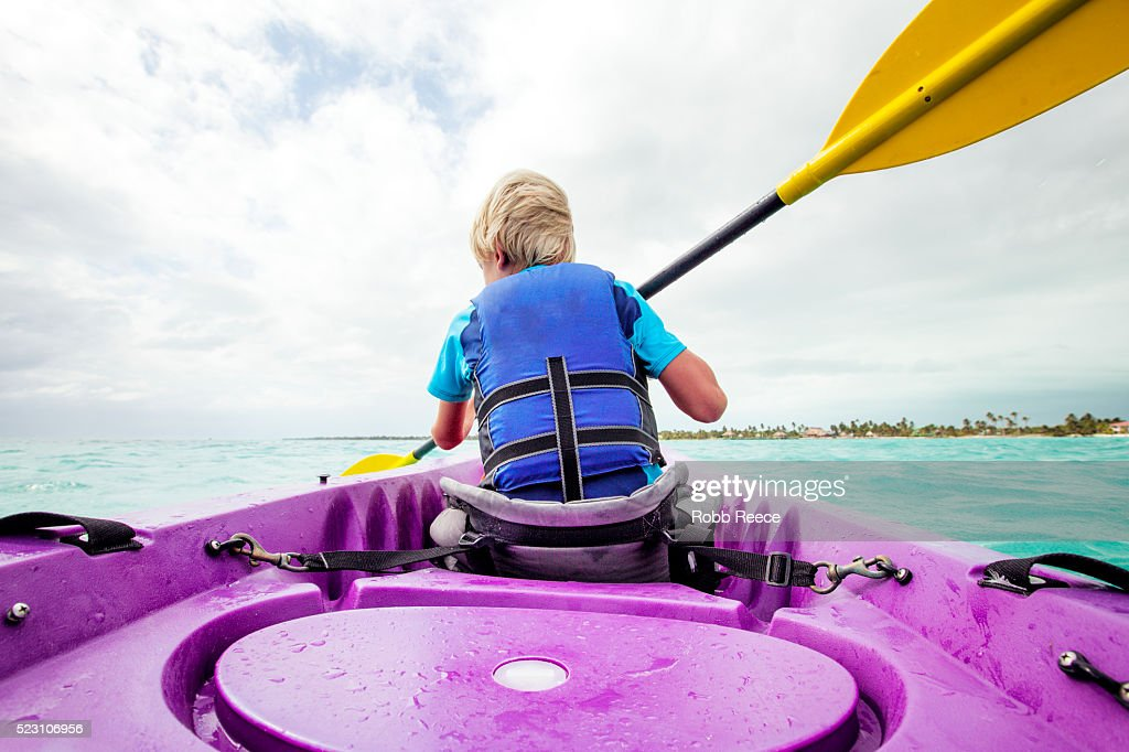 A young boy paddling a sea kayak on the ocean in Belize : Stock Photo