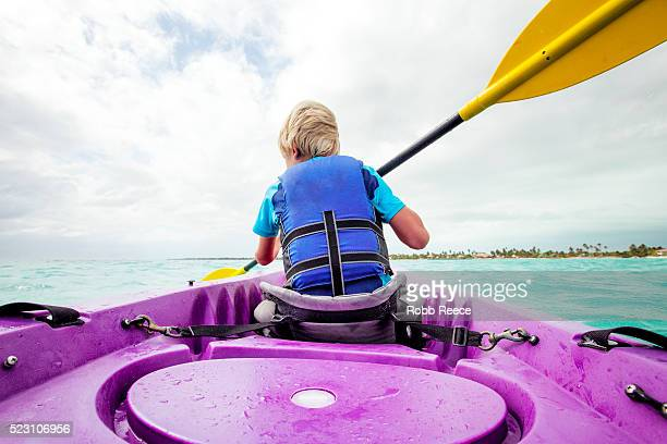 a young boy paddling a sea kayak on the ocean in belize - robb reece stock pictures, royalty-free photos & images