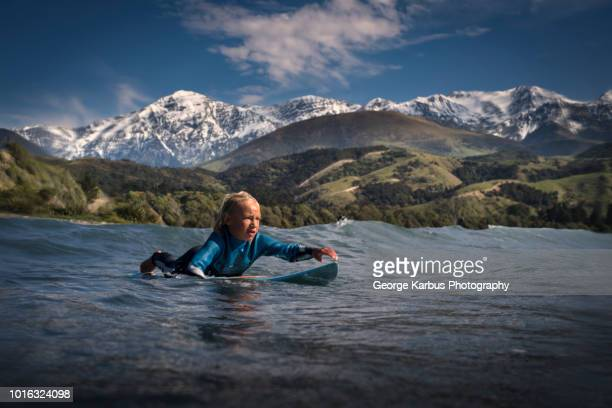 young boy paddling on surfboard in sea, kaikoura, gisborne, new zealand - innocence stock pictures, royalty-free photos & images