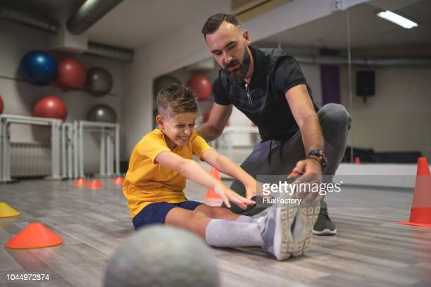 young boy painfully stretching legs - sports medicine stock pictures, royalty-free photos & images
