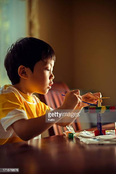 Young boy painting wooden airplane