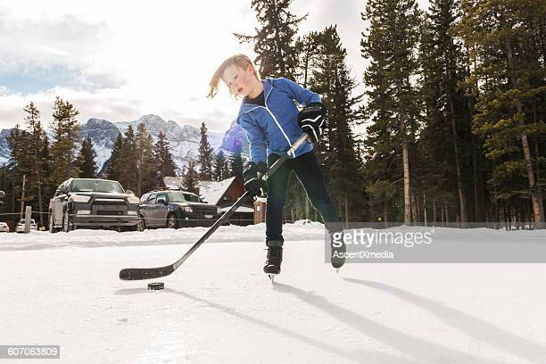 Young boy palys hockey on commuinty pond,mountains