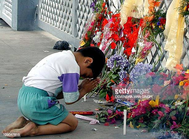 A young boy pays his respects to the late King and Queen of Nepal at the gates of the Royal Palace in Kathmandu 05 2001 A curfew was reimposed in the...