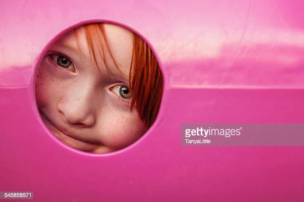 Young boy peeking through hole in playground tunnel