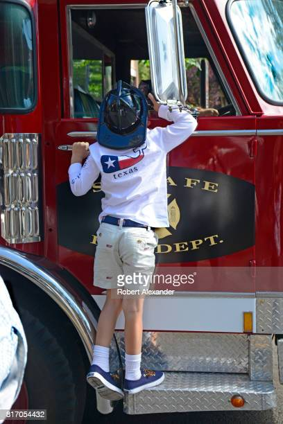 A young boy peeks into the cab of a fire engine on display at a Fourth of July celebration in Santa Fe New Mexico