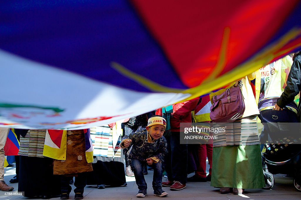 A young boy peeks underneath a Tibetan flag during a Free Tibet rally outside Downing Street in London on March 15, 2014. The annual march marks the anniversary of Tibetans' uprising against Chinese rule on March 10, 1959.