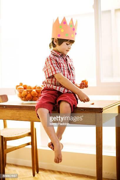 Young boy peeling an orange